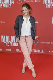 Nikola Kastner teamed a patterned gray down jacket with a white tunic and pink drawstring pants for a cozy yet stylish finish at the premiere of 'The Family.'