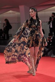 Tao Okamoto swept onto the red carpet in a Chanel print mini dress and a matching wrap during the Venice Film Festival premiere of 'Manhunt.'