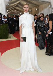 Karlie Kloss arrived for the Met Gala in ultra-elegant style wearing this caped white coat by Brandon Maxwell.
