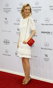 For a splash of color to her white outfit, Eva Herzigova accessorized with a chic red chain-strap bag.