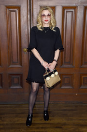 Courtney Love looked playfully chic in a pompom-trimmed LBD by Marc Jacobs during the brand's Spring 2018 show.