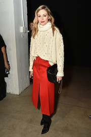 Olivia Palermo paired her sweater with a red A-line skirt.