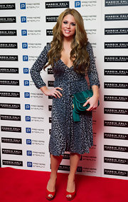 Bianca Gascoigne added to the exotic vibe of her wrap dress with a tasseled teal clutch.