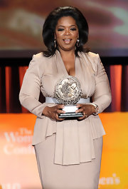 Oprah wears a Victoria Beckham nude toned dress when she receives her award at the Maria Shriver Women's Conference.
