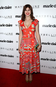 Alexandra Daddario sealed off her look with a gold and turquoise clutch.