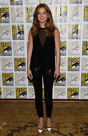 Emily paired her blouse with a pair of five-pocket leather leggings.