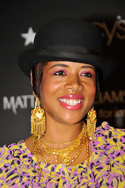 Kelis amped her look up with a heap of golden accessories. Gilded chain embellished earrings rounded out her look.