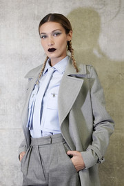 Bella Hadid posed backstage at the Max Mara Spring 2020 show wearing a baby-blue button-down shirt with a gray trench coat and matching trousers.