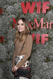 Suki Waterhouse arrived for the InStyle Max Mara Women in Film celebration carrying a black, red, and gold shoulder bag.