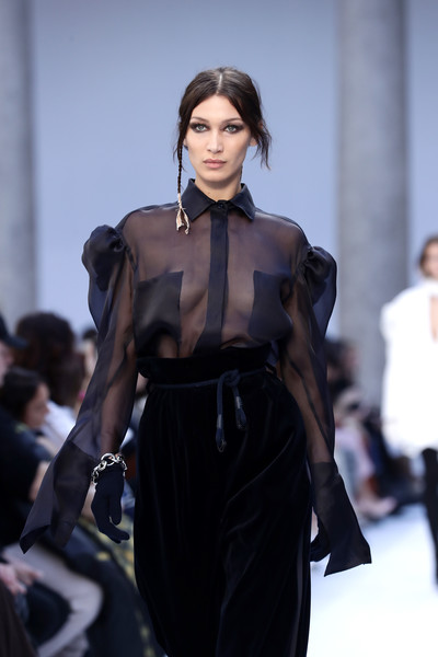 Bella Hadid walked the Max Mara runway wearing a link bracelet with a sheer blouse and velvet pants.