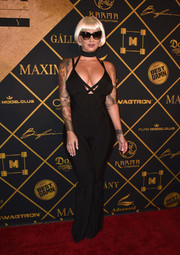 Amber Rose wrapped up her famous curves in a low-cut black bandage jumpsuit by Herve Leger for the Maxim Hot 100 Party.