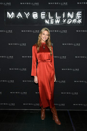 Martha Hunt attended the Maybelline Fashion Week party wearing a long-sleeve red silk dress.