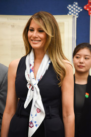 Melania Trump styled a plain black jumpsuit with a printed scarf by Hermes for her visit to the Bak Middle School of the Arts.