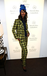 Iman stood out at Fashion Week in a unique ensemble consisting of a yellow plaid suit and an iridescent turban.