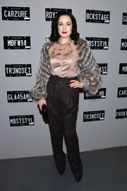 Dita Von Teese opted for a pair of charcoal slacks instead of a skirt to pair with her glam blouse.