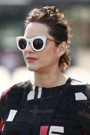 Marion Cotillard went for bold styling with a pair of thick-rimmed cateye shades.