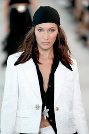 Bella Hadid tamed her messy tresses with a black head scarf for the Michael Kors runway show.