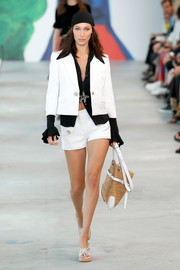 Bella Hadid looked cool in a white short suit teamed with a black shirt while walking the Michael Kors runway.