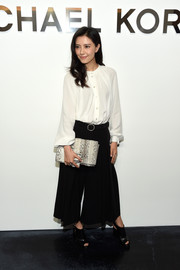 Gao Yuan Yuan looked conservative in a loose, long-sleeve white blouse at the Michael Kors fashion show.