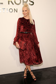Poppy Delevingne kept it prim in a long-sleeve red damask dress by Michael Kors during the label's fashion show.
