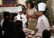 Michelle joined in the festive holiday baking wearing a gold lame' skirt suit. So Jackie O!
