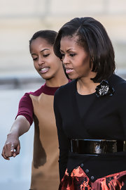 Michelle Obama cinched her cardigan with an oversized black patent leather belt for added flair.