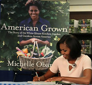 Michelle Obama looked fetching in a pink knit top spruced up with a flower brooch while signing copies of her book.