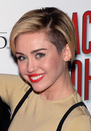 Miley Cyrus infused some color into her neutral look with a swipe of bright red lipstick.