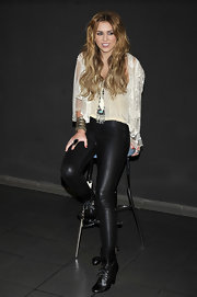 Miley covered up in black leather leggings  paired with au courant lace up ankle boots. A trendy lace blouse sweetened Miley's look.