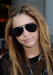 "Miley wore a gunmetal colored pair of super dark ""Tiresia"" aviator-style sunglasses."