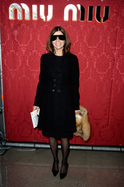 Carine Roitfeld kept cozy in a black wool coat during the Miu Miu fashion show.