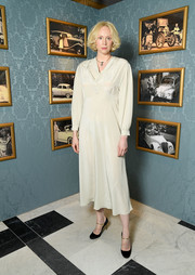 Gwendoline Christie was vintage-chic in this long-sleeve ivory midi dress by Miu Miu during the brand's Cruise Collection show.