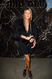 Anna dello Russo looked relatively tame in a black feather cape layered over an LBD at the Miu Miu fashion show.