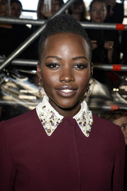 Lupita Nyong'o styled her short curls into a cool fauxhawk for the Miu Miu fashion show.