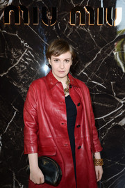 Lena Dunham complemented her red leather coat with a crescent-shaped black clutch by Prada when she attended the Miu Miu fashion show.