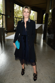 Dianna Agron layered a navy coat with an embellished collar over a gauzy dress for a classy finish at the Miu Miu fashion show.