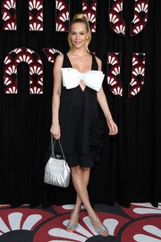 Poppy Delevingne looked cute in a black-and-white Miu Miu dress with oversized bow detail and a ruffle hem during the brand's Fall 2020 show.