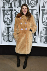 Anna dello Russo attended the Miu Miu Fall 2018 show looking luxe in a tan wool coat with flower buttons.