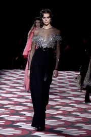 Kaia Gerber looked ultra elegant in a black gown with a sheer, beaded bodice while walking the Miu Miu Fall 2020 runway.