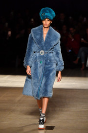 Joan Smalls looked luxuriously cozy in a blue fur coat while walking the Miu Miu show.