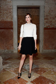 Dakota Johnson paired her cute top with a flared black mini skirt.