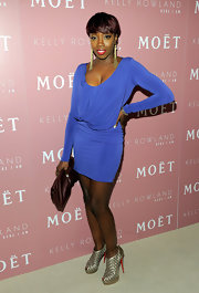 Estelle donned a blue knit body-con dress with a draped bodice for Kelly Rowland's album launch. Gold shoulder-dusters completed her party style.