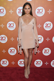 Chrissy Teigen chose a slinky nude cold-shoulder dress by Juan Carlos Obando for Mohegan Sun's 20th anniversary party.