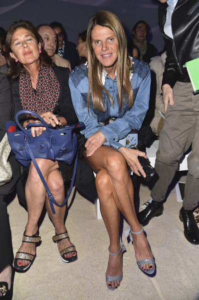 Anna dello Russo sat front row at the Moncler Gamme Rouge fashion show wearing a Miu Miu mini dress that featured a blue denim top and a black silk skirt.