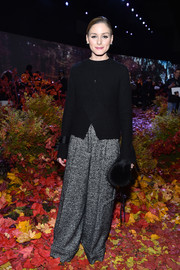 Olivia Palermo covered up in a black sweater with a crossover front for the Moncler Gamme Rouge fashion show.