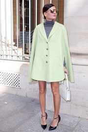 Giovanna Battaglia layered a loose mint-green coat over a gray turtleneck for the Moncler Gamme Rouge fashion show.