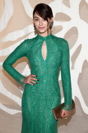 Emmy Rossum paired a metallic gold Jimmy Choo clutch with a green cocktail dress for a breathtaking look during the Monique Lhuillier fashion show.
