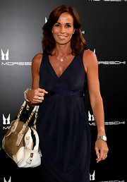 Cristina Parodi carried a roomy suede shoulder bag as she attended the opening of Moreschi.