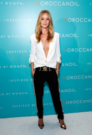 For her footwear, Rosie Huntington-Whiteley chose black Anthony Vaccarello x Versus Versace sandals featuring edgy gold detailing.