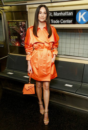 Kacey Musgraves matched her coat with an orange croc-embossed wristlet by Moschino.
